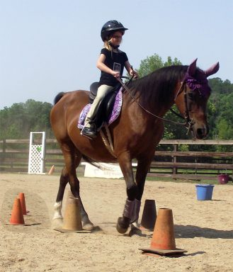 student and pony riding through obstacle course
