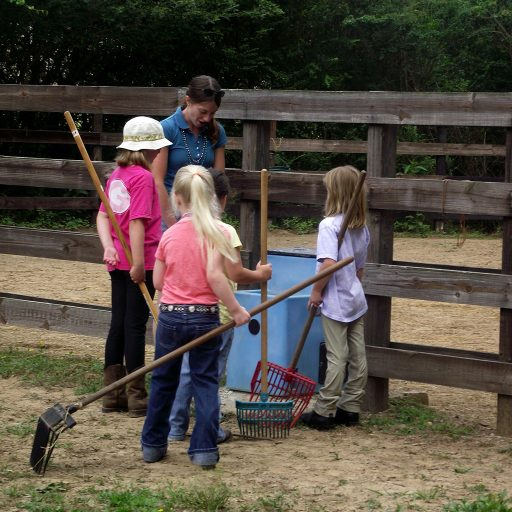 unmounted barn lesson teaching students to clean pasture waterers