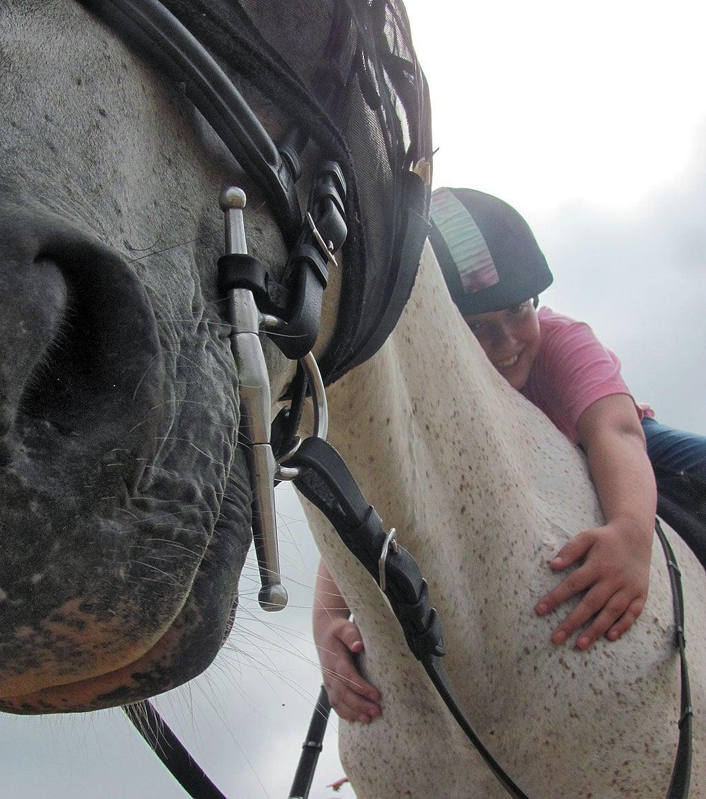 HorseSense student hugs lesson horse